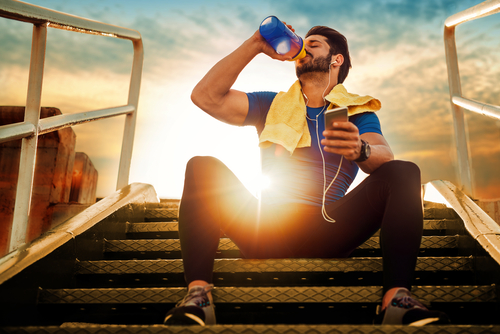 Athlete drinking water during a walk at sunset
