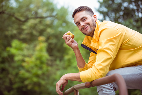 Man sitting on park bench eating an apple snack