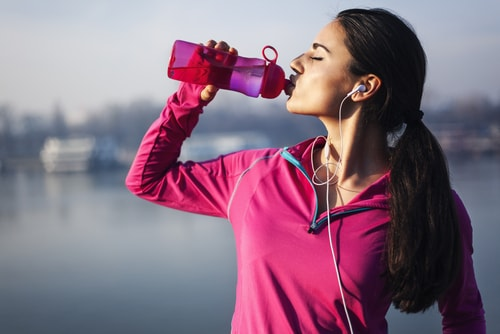 Woman drinking water after a run or walk