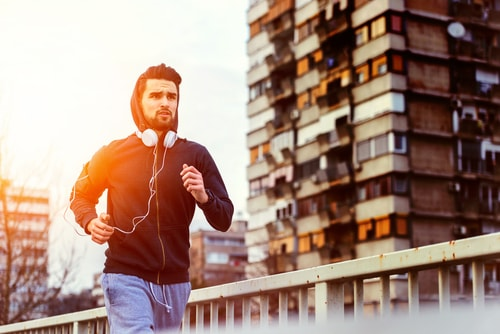 Man doing jog or intense fitness walk in city