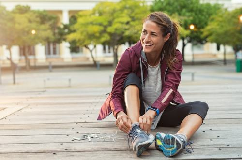 Fit woman sitting and tying shoes during a walk