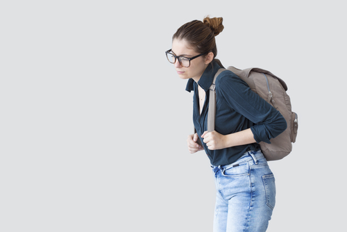 Woman with poor posture due to a heavy backpack