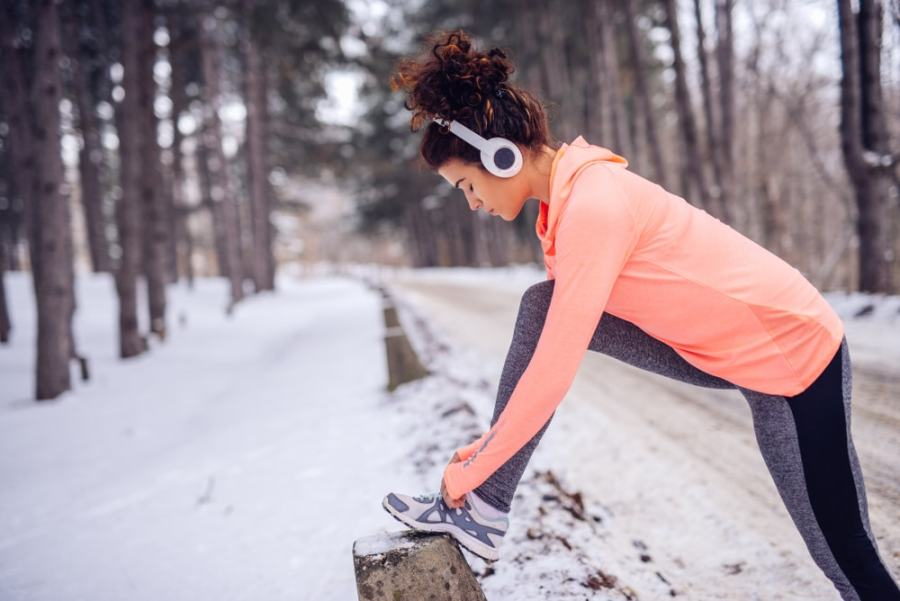 Woman tying her shoes during a snowy walk or jog