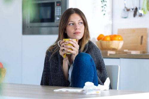 Woman with cold drinking tea at home
