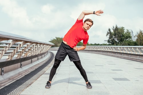 Man doing side stretch during a jog