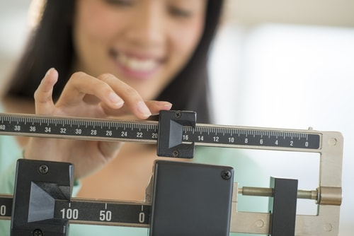 Woman checking scale - weight control concept
