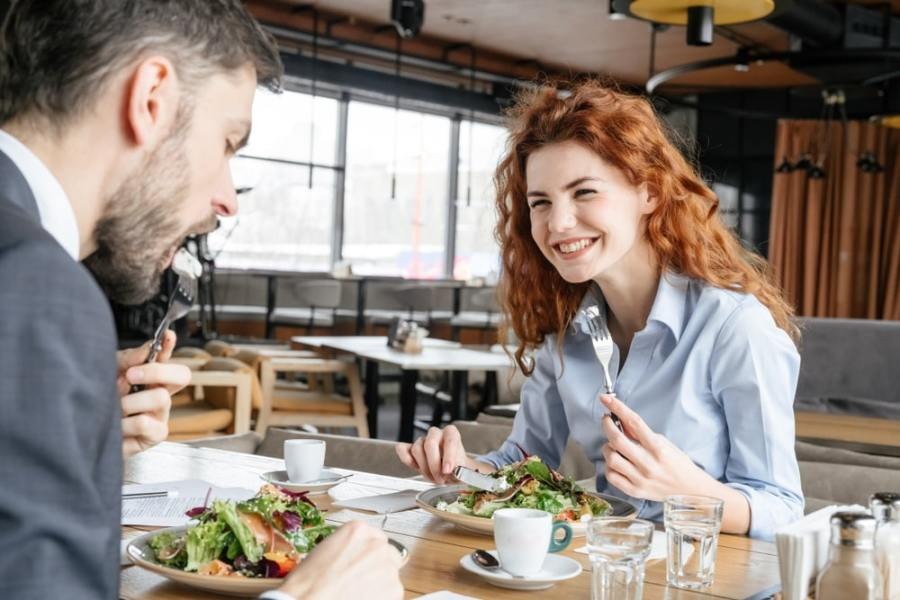 Man and woman eating healthy business lunch
