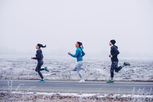 3 people running for fitness on a winter road