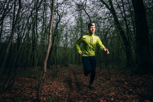 Man jogging in woods with reflective headgear
