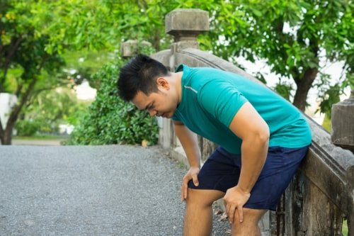 Man doubled over exhausted from exercise in heat
