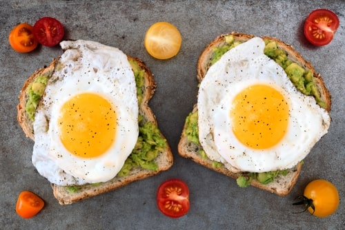 Healthy avocado toast and egg with tomatoes