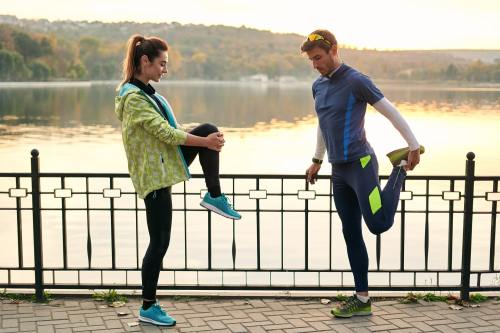 Fit couple stretching before walk near lake