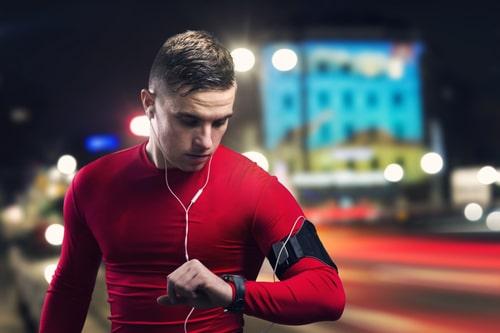 Man checking watch after night walk or run