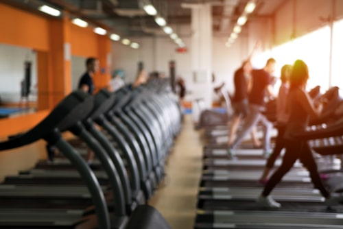 Gym layout with cardio equipment blurred