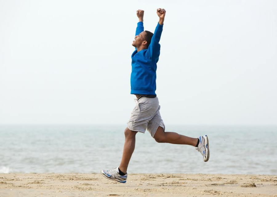 Man celebrating while jogging near the beach