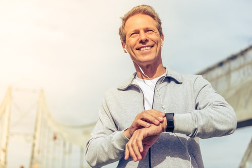 Fit middle-aged man checking smart watch