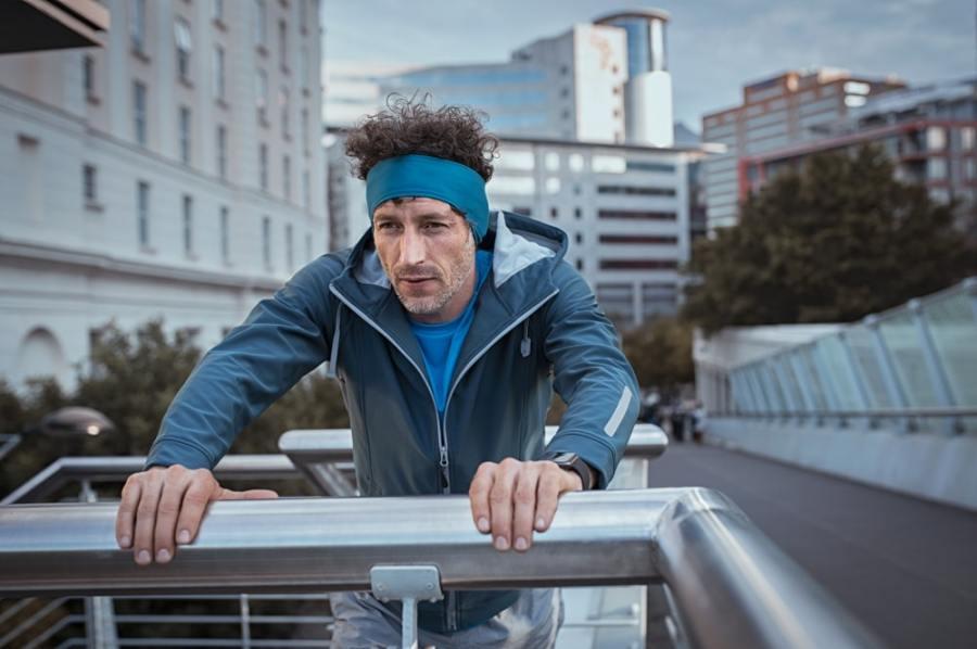 Man resting on footbridge after fitness walk or run