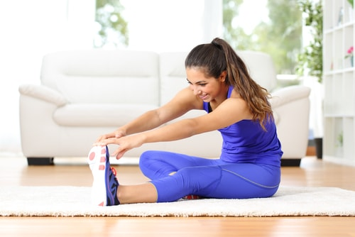 Woman stretching on rug in living room
