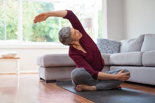 Senior woman doing yoga at home in living room