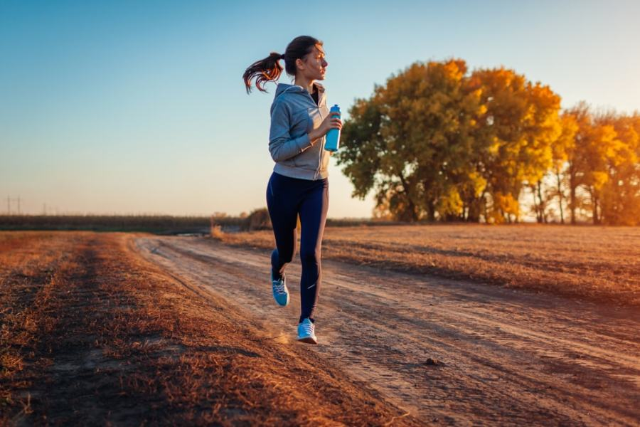 Woman jogging on country road in morning