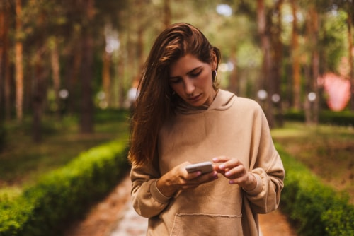 Woman checking phone during walk in park