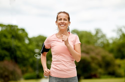 Smiling woman power walking for fitness