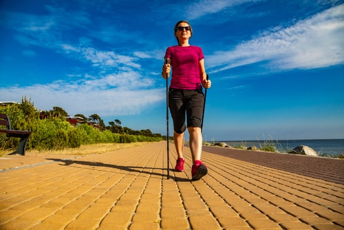 Woman Nordic Walking near the ocean
