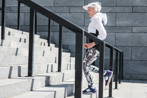 Senior woman walking stairs for fitness