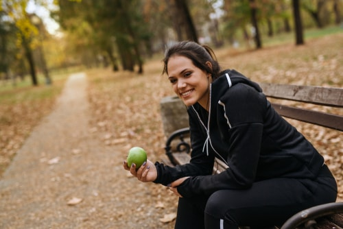 Jogger sitting on park bench eating apple