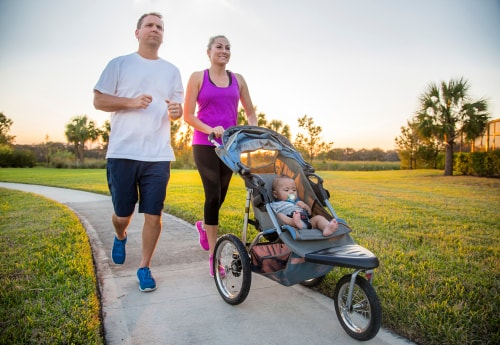 Couple fitness walking outside with baby stroller