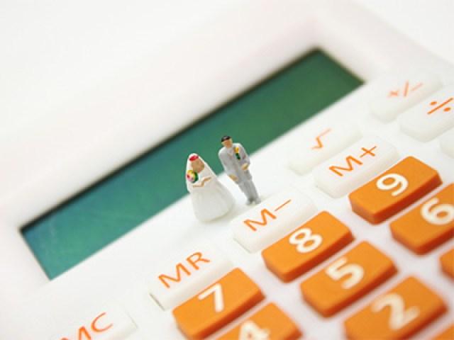 calculatrice blanche et orange avec deux figurines de mariés posés devant l'écran