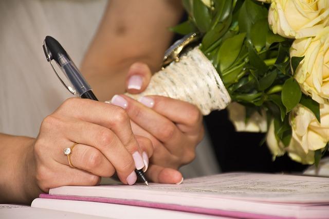 la mariée signe le registre du mariage civil avec son bouquet à la main