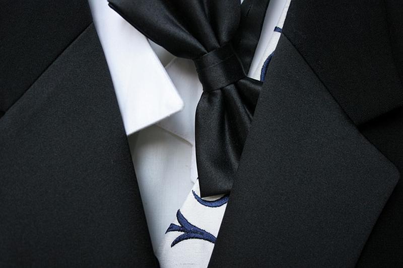 costume de marié noir et blanc avec cravate et noeud papillon en gros plan