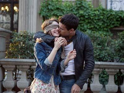 Jeune femme aux yeux bandés dans les bras de son amoureux qui l'embrasse
