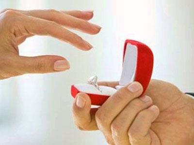 Main de femme prête à saisir une bague de fiancailles dans un écrin rouge présenté par un homme