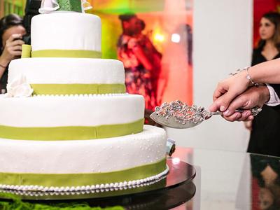 Couple de mariés prêts à couper un wedding cake blanc et vert sur 4 étages
