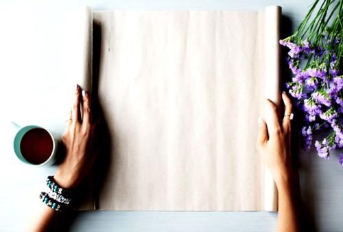 Une femme déroule un rouleur de papier texturé pour créer un faire part de première communion