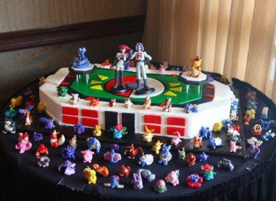 Gateau d'anniversaire pokemon en forme de stadium avec ses figurines pokemon