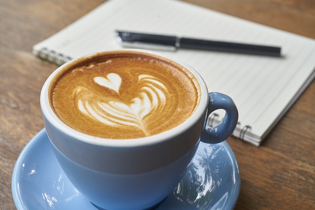 Tasse de café coeur et bloc note avec un stylo pour rédiger ses voeux de mariage