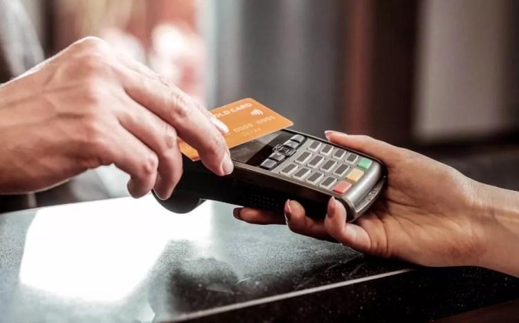 Un cliente que paga con una máquina de tarjetas de crédito sin contacto