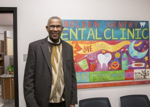 Nolden Gentry stands next to a sign welcoming people to the dental clinic named in his honor at Scavo High School. Courtesy: Des Moines Public Schools.