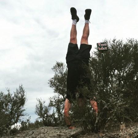 man doing handstand near bushes