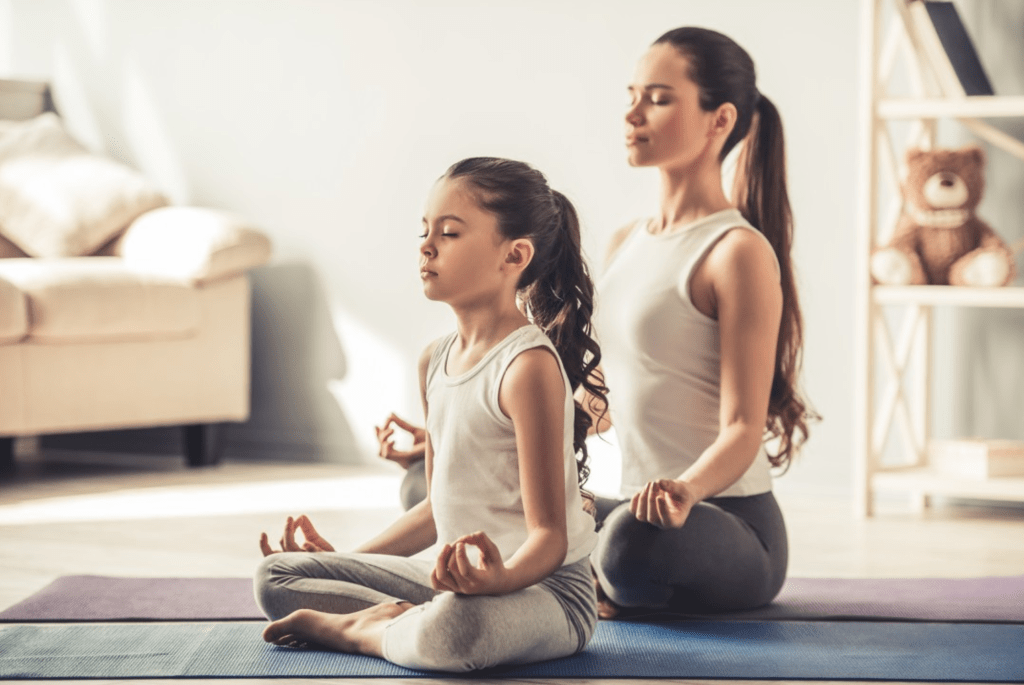 Mother and Daughter meditating on yoga mats