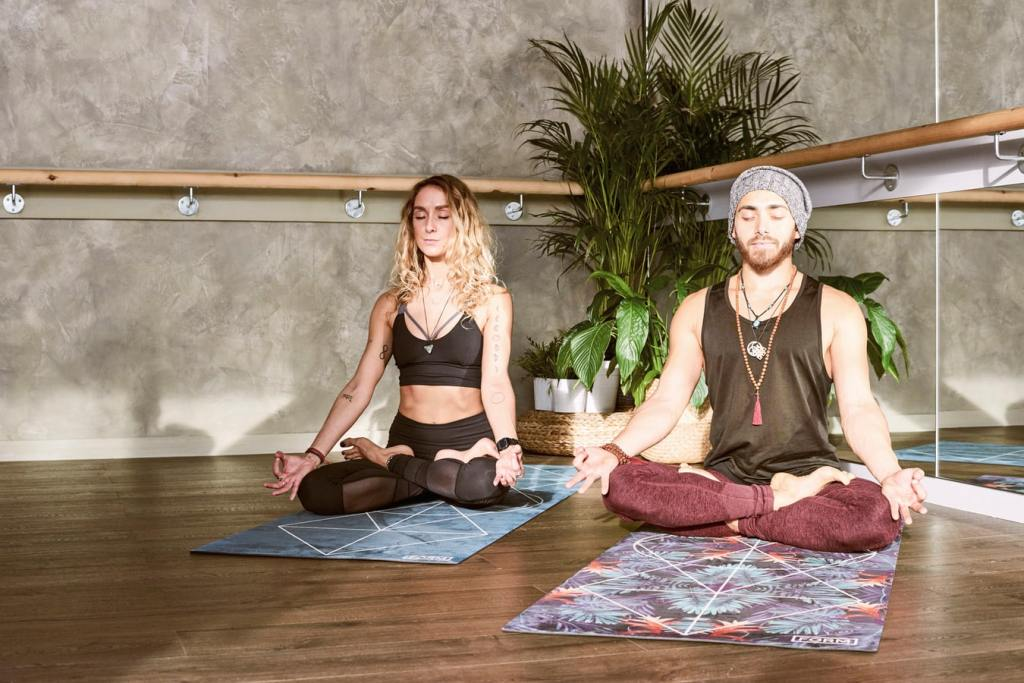 man and woman meditating on yoga mats in studio