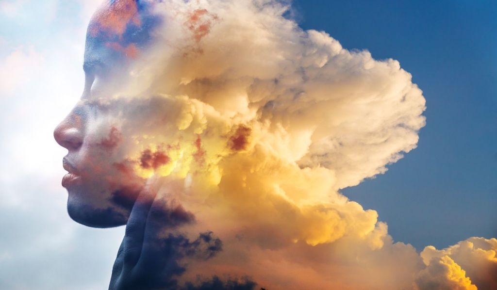meditating head merged with clouds ins sunset
