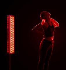 woman with back pain showing red light therapy