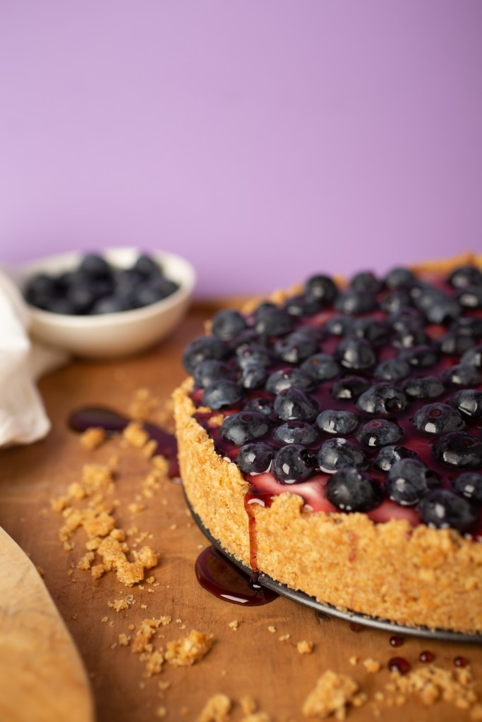 A blueberry cheesecake with a purple background