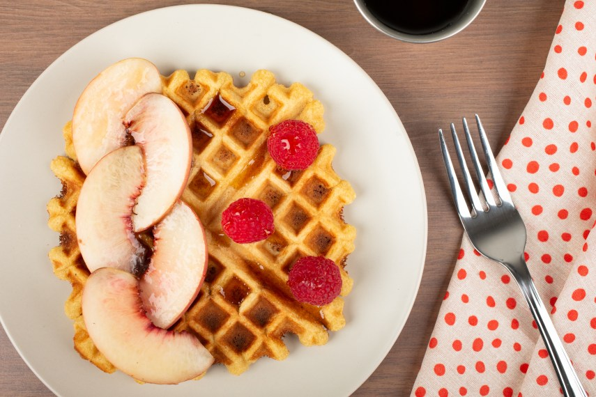 peach waffles on a plate with a fork on the side
