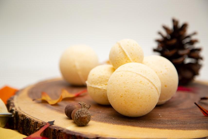pumpkin spice bath bombs on a wooden plate