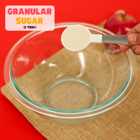 measuring spoon pouring sugar into a bowl